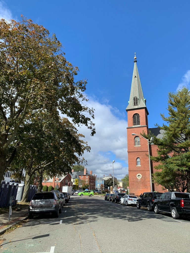 Salem street with spire building, trees, and cars