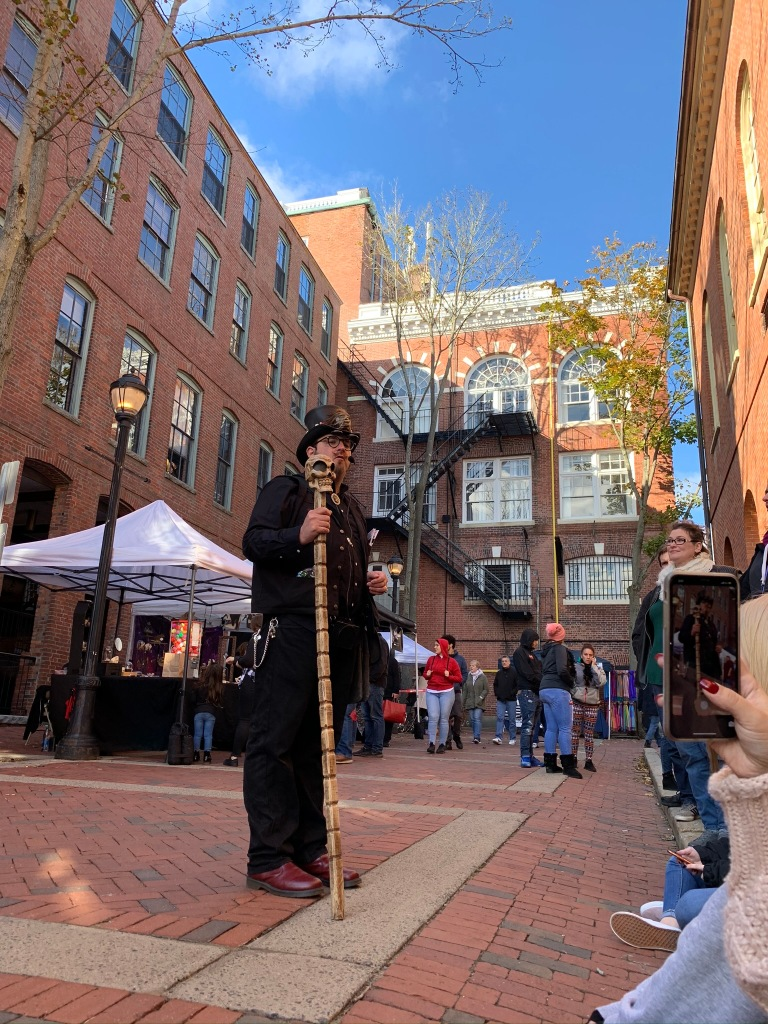 Dr. Vitka, tour guide for Spellbound Tours, stands in front of several visitors sitting down on curb. Dr. Vitka wears all black holding a staff/cane topped with a grimacing skull. Background is a red building encompassing the scene.